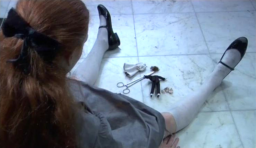 A girl sitting on the ground with a doll and scissors between her legs on the floor.