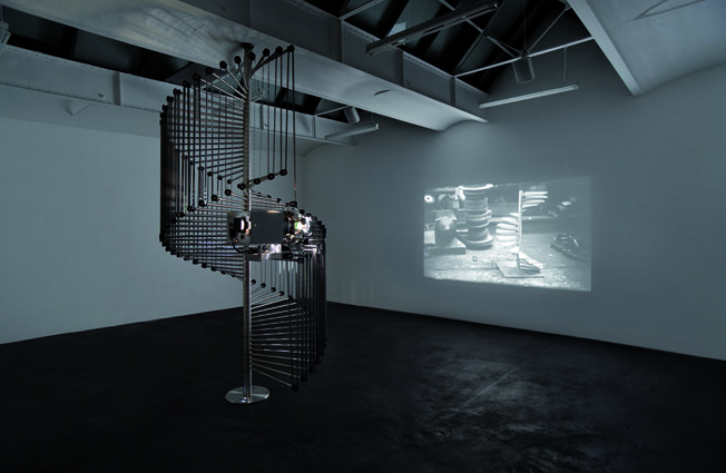 Simon Starling Wilhelm Noack oHG, 2006. Purpose built loop machine, 35 mm film projector, 35 mm b/w film with sound, 4 min, 407 x ø 192 cm, projected dimensions variable. Installation view neugerriemschneider, Berlin. Collection: Museum Folkwang, Essen. © Simon Starling and Museum Folkwang, Essen