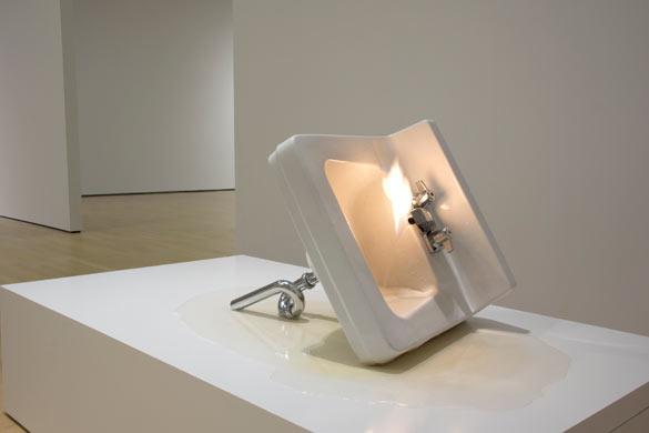Michel de Broin, Étant Donnés, 2013, Eau, gas, lavabo, 166 x 92 x 46 cm. Un mélange d'eau et de feu s'écoule d'un lavabo couché sur le côté. La coexistence d'éléments opposés se manifeste dans un objet familier devenu étrange.