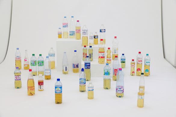 """Gabriel Kuri, """"bottled water E.d.E. 2"""", 2013, bouteilles, mélange d'alcool, socle, papier, dans le cadre de l'exposition au Parc Saint Léger """"bottled water branded water"""" crédit Parc Saint Léger"""